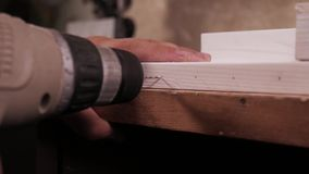 关闭使用一个电手钻的木工作者通过操练孔 股票录像