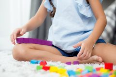 关闭使用与五颜六色的塑料块的手孩子在地板 免版税图库摄影