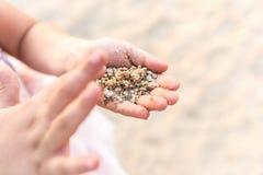 关闭使用与沙子的孩子手 免版税库存照片