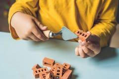 关闭使用与真正的小黏土砖的儿童的手在 库存图片
