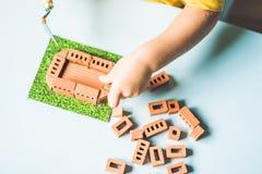 关闭使用与真正的小黏土砖的儿童的手在 免版税库存照片