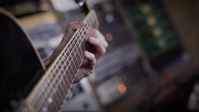 关闭使用在一台仪器的一个低音吉他弹奏者的射击在录音室 股票录像