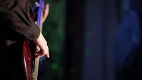 关闭使用在摇滚乐音乐会的红色大耳鲈吉他的低音吉他弹奏者 股票录像