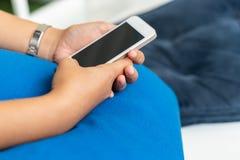 关闭使用在触摸屏上的妇女流动巧妙的电话有警察的 免版税库存照片