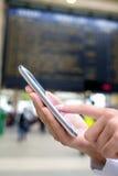 关闭使用她的手机的手妇女在火车站, b 免版税库存照片
