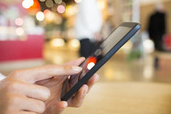 关闭使用她的手机的手妇女在火车站 免版税库存图片