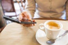 关闭使用她的手机的手妇女在餐馆,咖啡馆 免版税库存照片