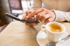 关闭使用她的手机的手妇女在餐馆,咖啡馆 免版税图库摄影