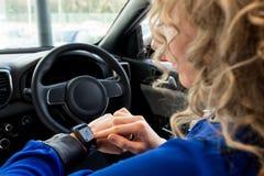 关闭使用巧妙的手表的妇女在汽车 图库摄影