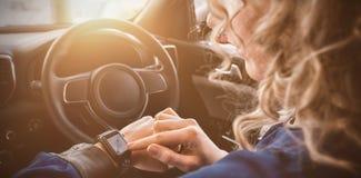 关闭使用巧妙的手表的妇女在汽车 库存照片