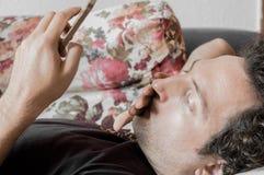 关闭使用巧妙的电话的一个轻松的白种人人在家说谎在长沙发在客厅 免版税库存图片