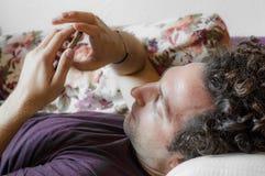 关闭使用巧妙的电话的一个轻松的白种人人在家说谎在长沙发在客厅 库存图片