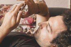 关闭使用巧妙的电话的一个轻松的白种人人在家说谎在长沙发在客厅 免版税库存照片