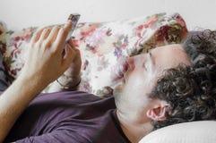 关闭使用巧妙的电话的一个轻松的白种人人在家说谎在长沙发在客厅 库存照片