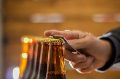 关闭使用开启者的一个人到瓶在被弄脏的背景的工艺啤酒 库存照片