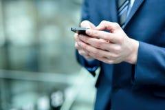关闭使用手机的一个人 免版税库存照片