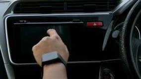 关闭使用汽车触摸屏显示器的人的射击手,在燃烧汽车前起动引擎  影视素材