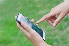 关闭使用流动巧妙的电话的一个人 免版税库存图片