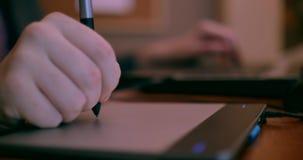 关闭使用片剂和便携式计算机4k滑的一位年轻设计师的手 股票视频