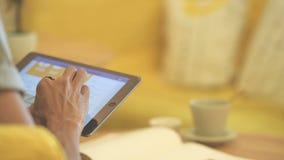 关闭使用片剂的手人在桌上的咖啡咖啡馆 影视素材
