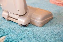 关闭使用的现代吸尘器的头,当吸尘一张厚实的堆白色地毯时 库存图片