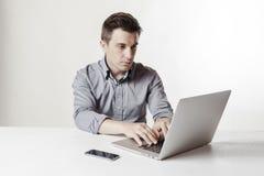 关闭使用膝上型计算机和手机的多任务商人的图象 免版税图库摄影