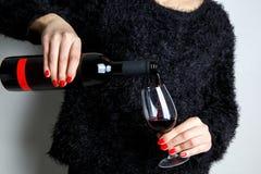 关闭倒红葡萄酒的一个少妇的手入从瓶的一块玻璃 库存图片