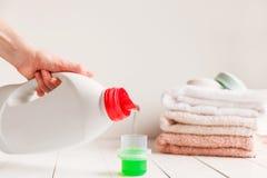 关闭倾吐液体洗涤剂的女性手入在白色土气桌上的盖帽与在背景的毛巾 库存图片