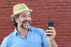 关闭倾斜对红色墙壁的一个成熟人使用手机 拿着智能手机的一个愉快的商人的画象 图库摄影