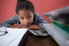 关闭假装作为女实业家的女孩画象倾斜在书桌 库存照片