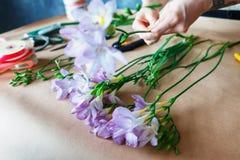 关闭做与紫色番红花的台式视图迷人的快乐的女性售货员花束 库存照片