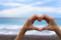 关闭做与蓝色海和天空的女性手心脏形状 免版税库存图片