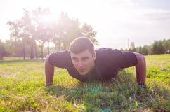 关闭做在草的一个人俯卧撑与天际在背景中 库存照片