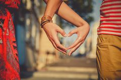 关闭做心脏形状用手的爱恋的夫妇在城市街道 夏令时 库存图片