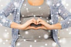 关闭做心脏的愉快的孕妇 库存图片