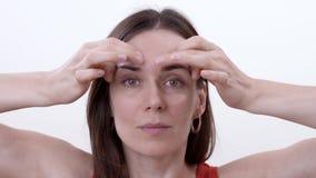 关闭做手指的水平的运动的在眼眉的深色的妇女减少在之间的皱痕 股票视频