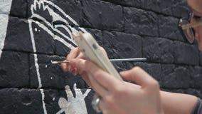 关闭做白色设计的年轻女性画家在咖啡店的黑砖墙 股票录像