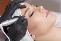 关闭做眼线膏永久构成的美容师 免版税图库摄影