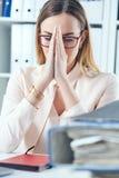 关闭做祈祷的手势的被注重的办公室妇女,当看堆文件她的工作场所时 免版税库存图片