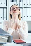关闭做祈祷的手势的被注重的办公室妇女,当看堆文件她的工作场所时 库存图片