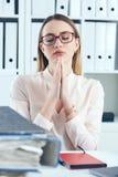 关闭做祈祷的手势的被注重的办公室妇女,当看堆文件她的工作场所时 免版税库存照片