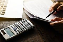 关闭做财务的手人并且在家计算在关于费用办公室的书桌上 储款、财务和经济概念 免版税图库摄影