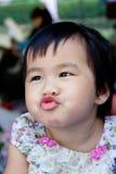 关闭做滑稽的嘴的可爱和逗人喜爱的亚裔婴孩的面孔 库存照片