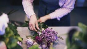 关闭做紫色花花束,掀动的妇女卖花人下来 股票录像
