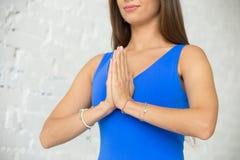 关闭做Namaste的一名年轻可爱的妇女 免版税库存照片