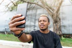 关闭做selfie的可爱的深色皮肤的人在手机 库存照片