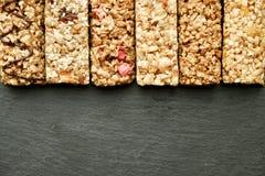 关闭健身食物用不同的种类的力量酒吧混杂的坚果 没有害处的素食甜点图的 背景 免版税库存照片