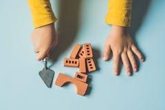 关闭儿童使用与真正的小黏土砖的` s手在 免版税库存照片