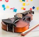 关闭儿童小提琴和弓,说谎在一张白色书桌上有与五颜六色的信件和数字的被弄脏的白板背景 免版税库存照片