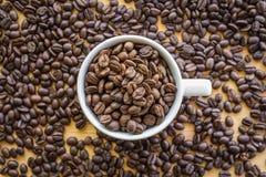 关闭充分加奶咖啡杯子咖啡豆背景 库存照片
